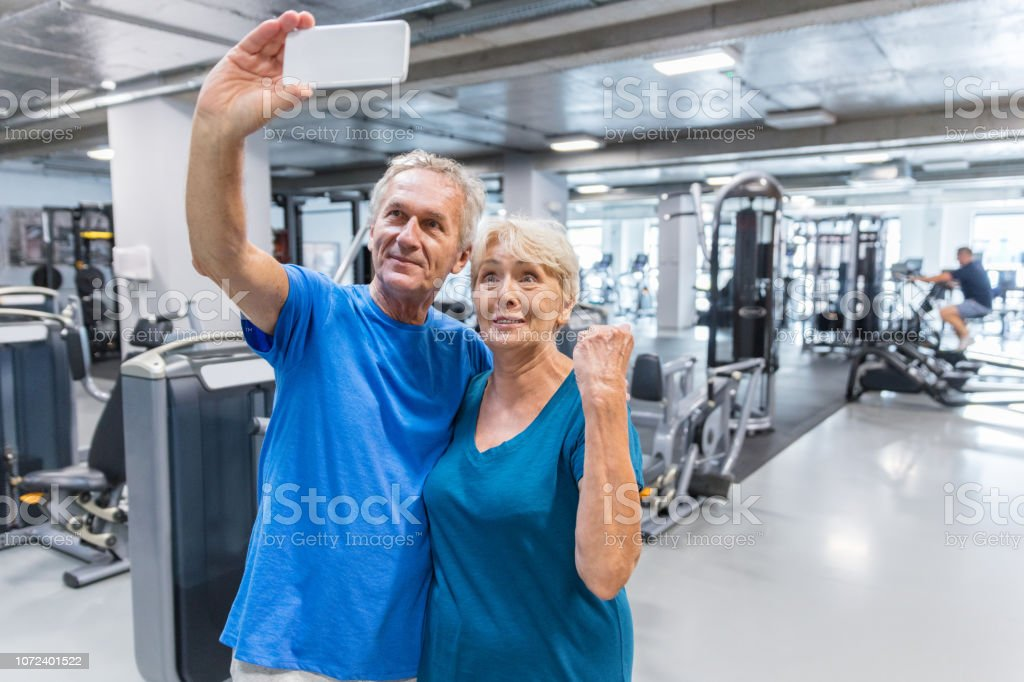 Senior couple making a selfie at fitness club stock photo