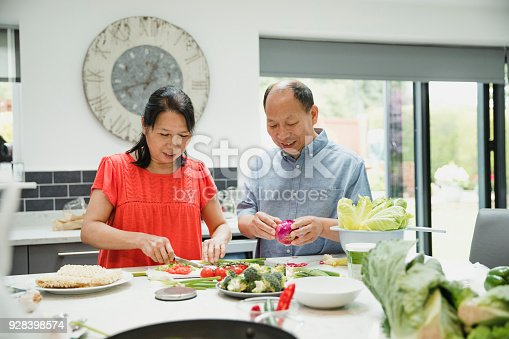 Senior couple are preparing vegetables together in the kitchen to make a stir fry.