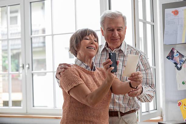 Senior Couple Making Copy of Old Photos stock photo