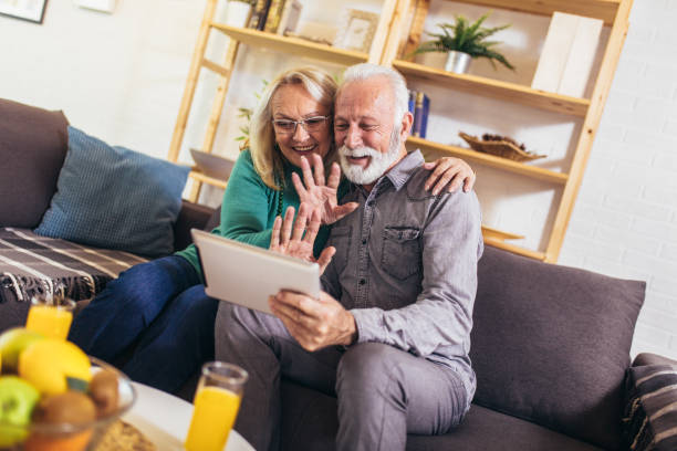 Senior couple making video call on digital tablet at home. stock photo