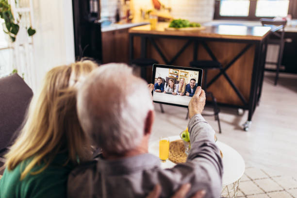 Senior couple making video call on digital tablet with their grandchildren and children stock photo