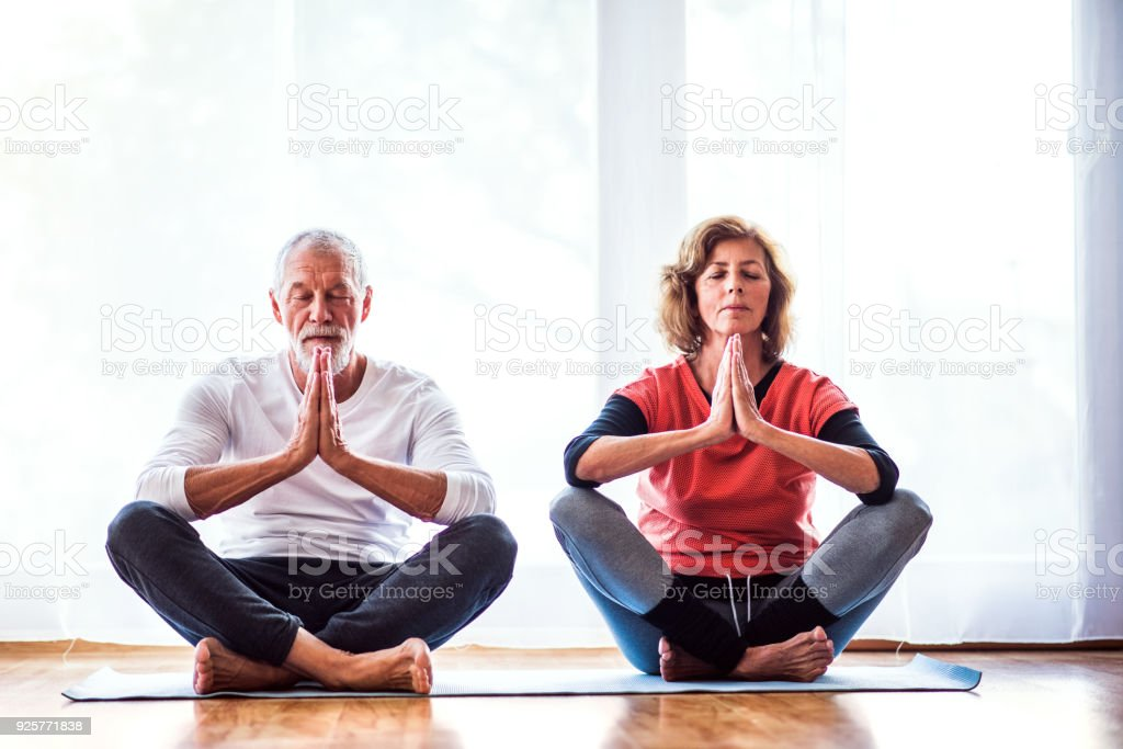 Senior couple meditating at home. stock photo