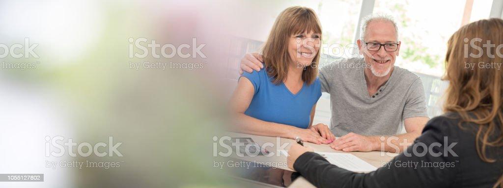 Senior couple meeting financial adviser stock photo