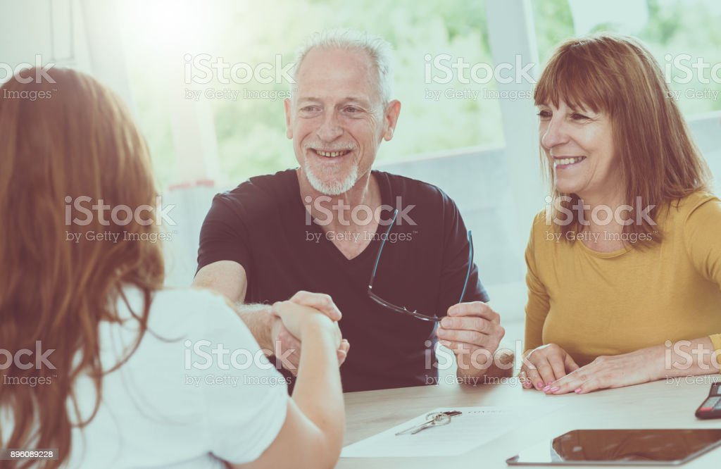 Senior couple meeting real estate agent, light effect stock photo