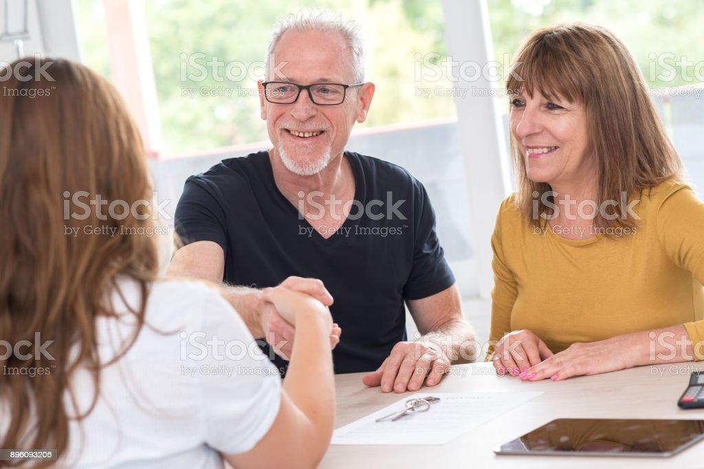Senior couple meeting real estate agent stock photo