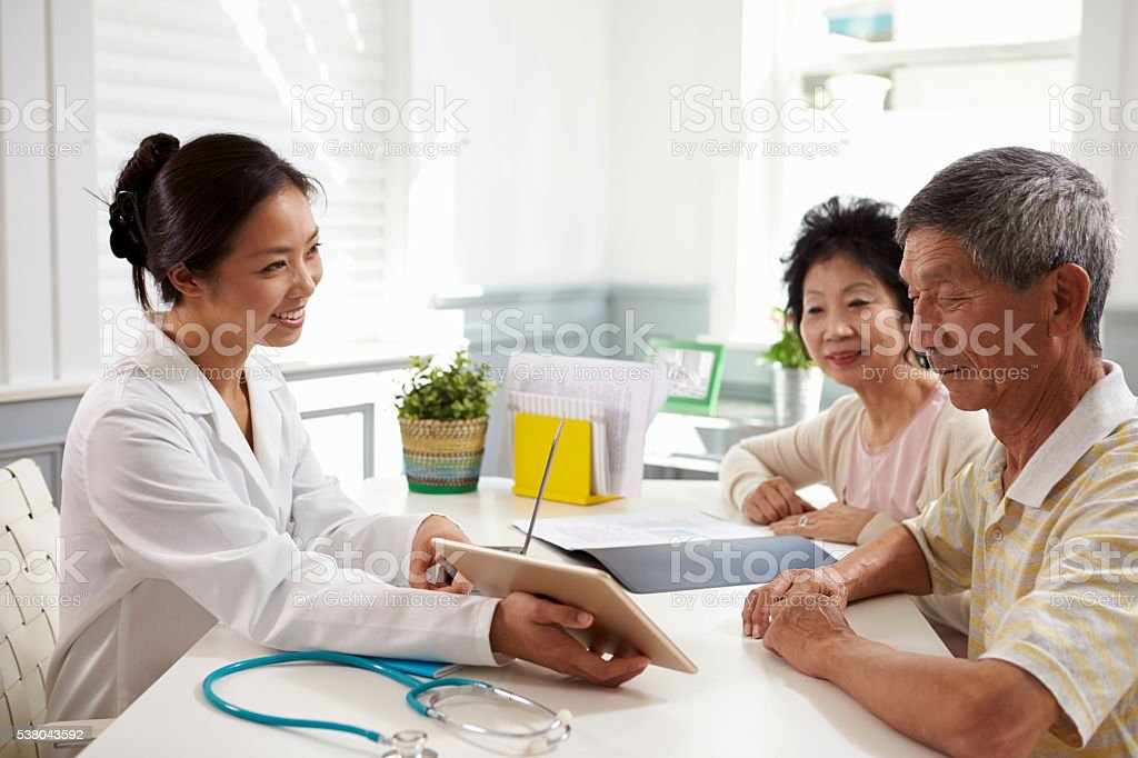 Senior Couple Meeting With Doctor In Office stock photo