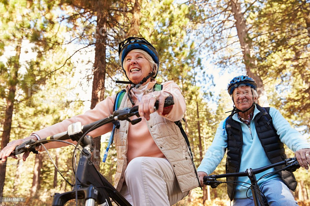 Senior couple mountain biking on a forest trail, low angle royalty-free stock photo