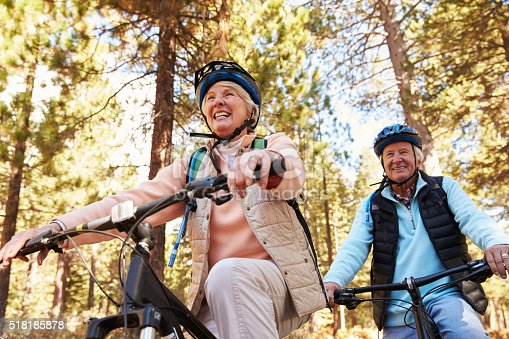 istock Senior couple mountain biking on a forest trail, low angle 518185878