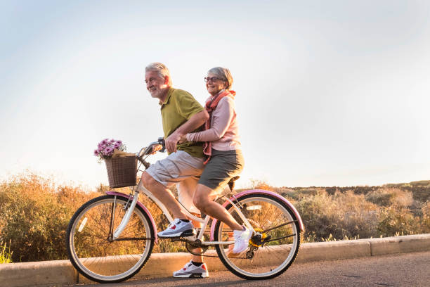 senior couple move with a bicycle together outdoor like children two senior man and woman together on  an old bicycle outdoor activity. Happiness and freedom from work concept. sunlight and smiles. always stock pictures, royalty-free photos & images