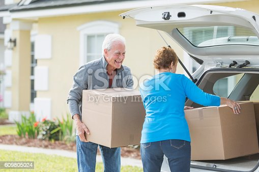 A senior couple lifting cardboard boxes into or out of the back of a car parked in the driveway of a house. They are moving, perhaps downsizing. The man is looking at his wife and laughing. Her back is to the camera.