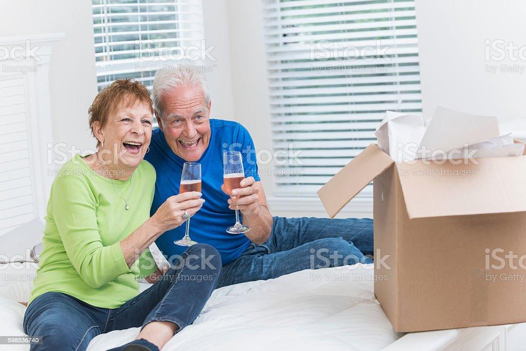 Senior couple moving house, celebrating with champagne stock photo