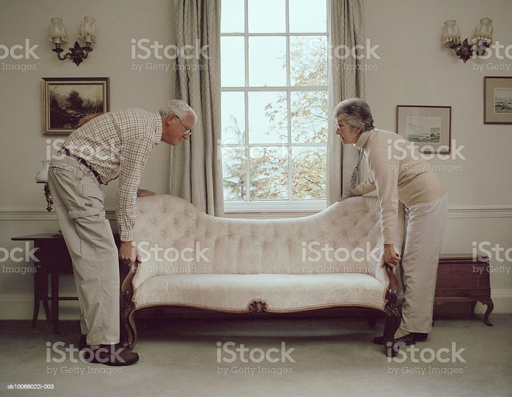 Senior couple moving sofa royalty-free stock photo