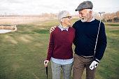 Senior couple going to play golf.