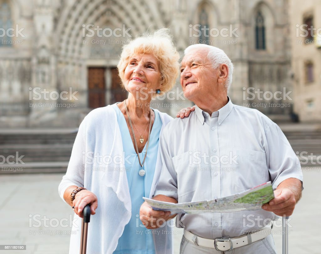 senior couple of tourists with map and city guide walking on str stock photo