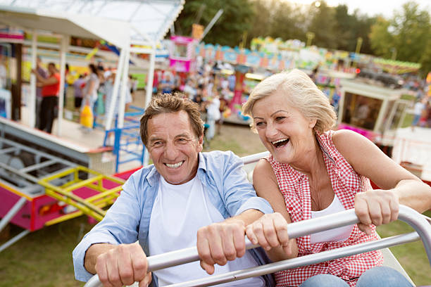 senior couple on a ride in amusement park - middle aged man dating bildbanksfoton och bilder