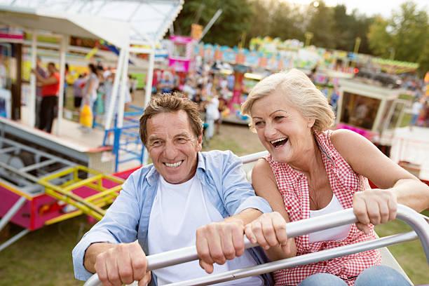 Senior couple on a ride in amusement park – Foto