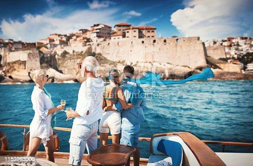 istock Senior couple on a sailing cruise looking at coastline. 1152263000