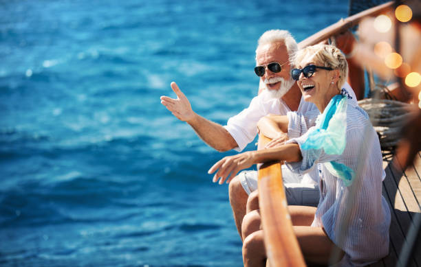 Senior couple on a sailing cruise. Closeup side view of mid 60's couple enjoying a sailing cruise during  summer vacation at seaside. mediterranean sea stock pictures, royalty-free photos & images