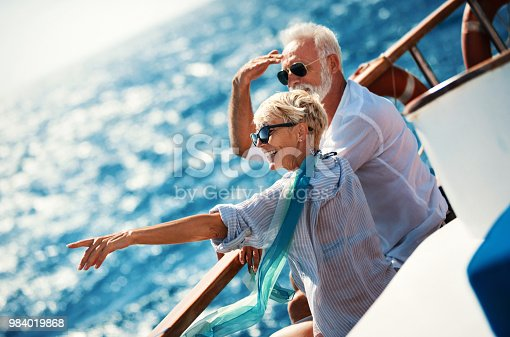 Closeup side view of mid 60's couple enjoying a sailing cruise during  summer vacation at seaside. They are leaning on deck railing and enjoying the view of the sea and horizon.