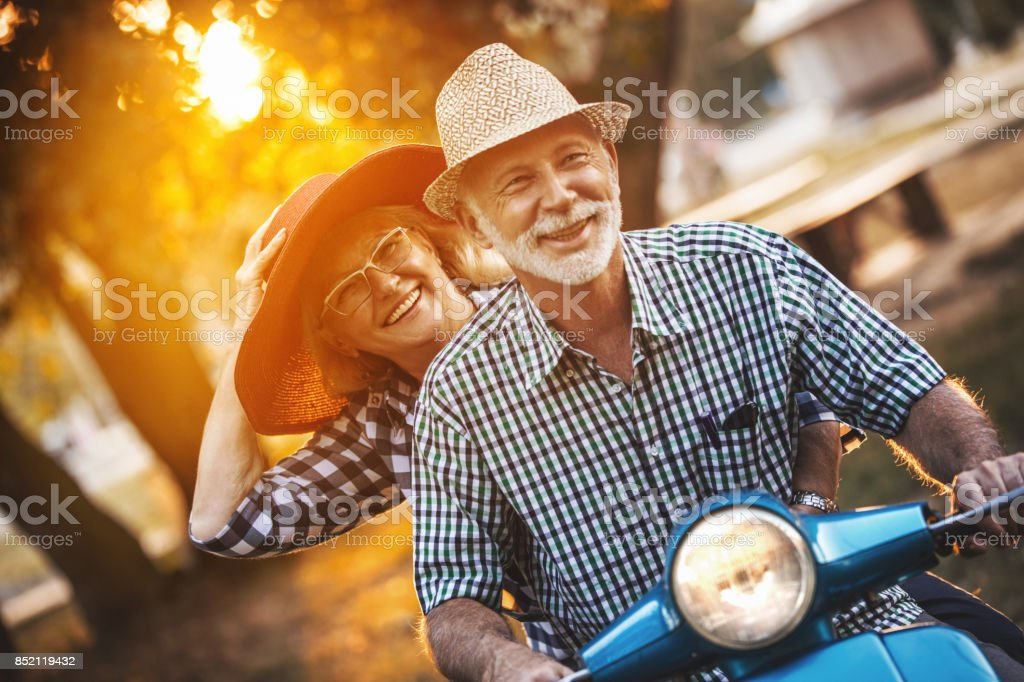 Senior couple on a scooter bike driving through city streets. stock photo