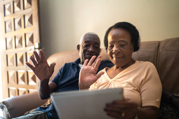 Senior couple on a video calling using a digital tablet at home stock photo