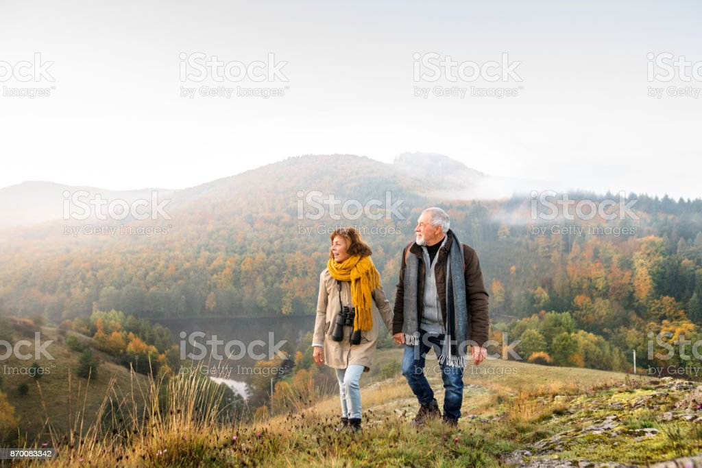 Senior couple on a walk in an autumn nature. stock photo