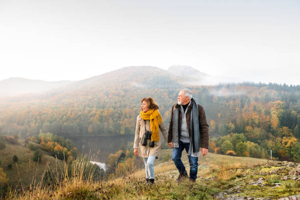 senior couple on a walk in an autumn nature. - hiking stock photos and pictures