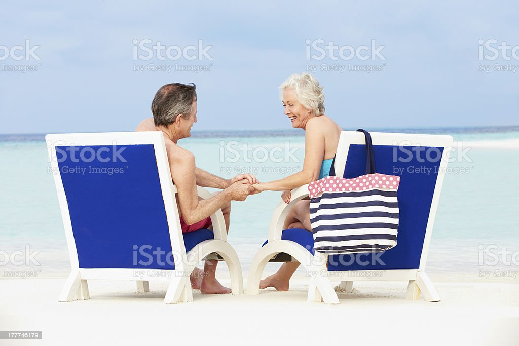 Senior Couple On Beach Relaxing In Chairs royalty-free stock photo