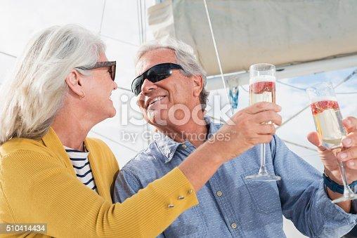 510491454 istock photo Senior couple on boat celebrating with champagne 510414434