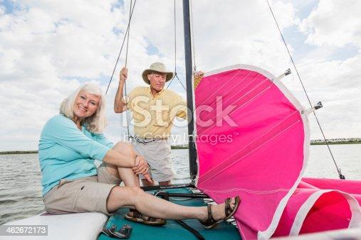 istock Senior couple on catamaran, hoisting sail 462672173