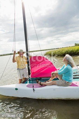 istock Senior couple on catamaran, man raising sail 472154463