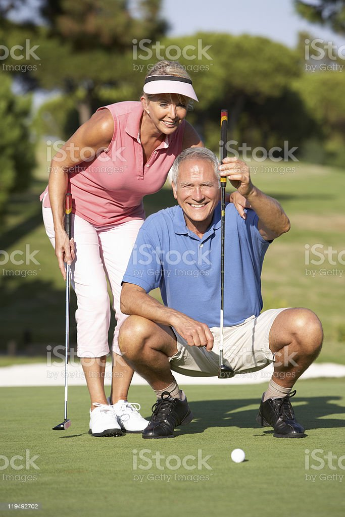 Senior Couple On Golf Course Lining Up Putt stock photo