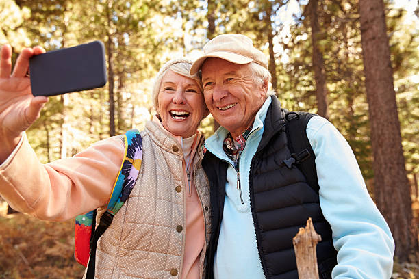 senior couple on hike in a forest taking a selfie - aktiva pensionärer utflykt bildbanksfoton och bilder