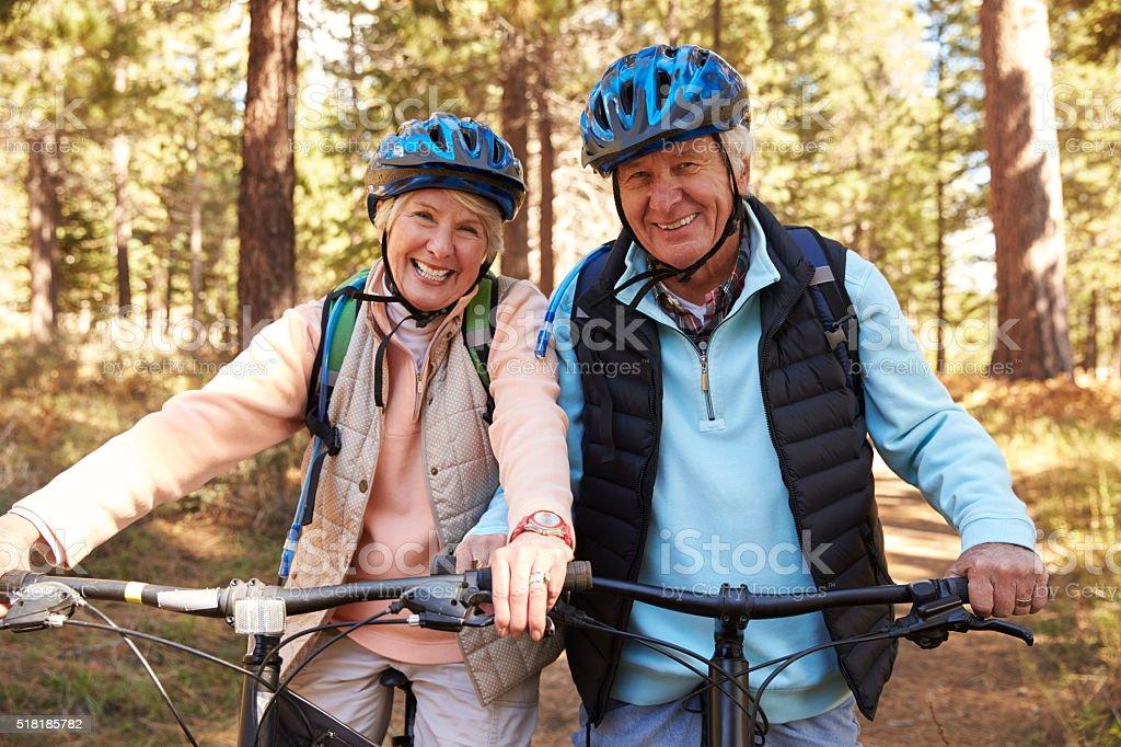 Senior couple on mountain bikes in a forest, portrait stock photo