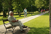 Senior man and woman sitting in park. Looking in the distance. People cycling, running and walking in the background.