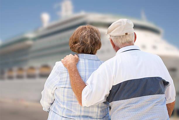 Altes Paar am Ufer mit Blick auf Kreuzfahrtschiffe – Foto
