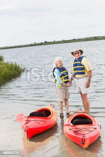 istock Senior couple on shore of lake with kayaks 488853753