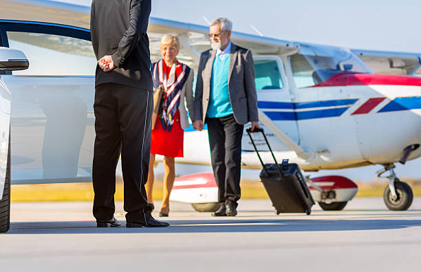 senior couple on the airport with waiting limousine - limousine service stock photos and pictures
