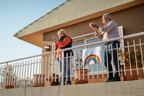 Senior-Paar auf ihre 70er Klatschen Hände auf Balkon mit einem handgezeichneten Regenbogen fix bei Bannister – Foto