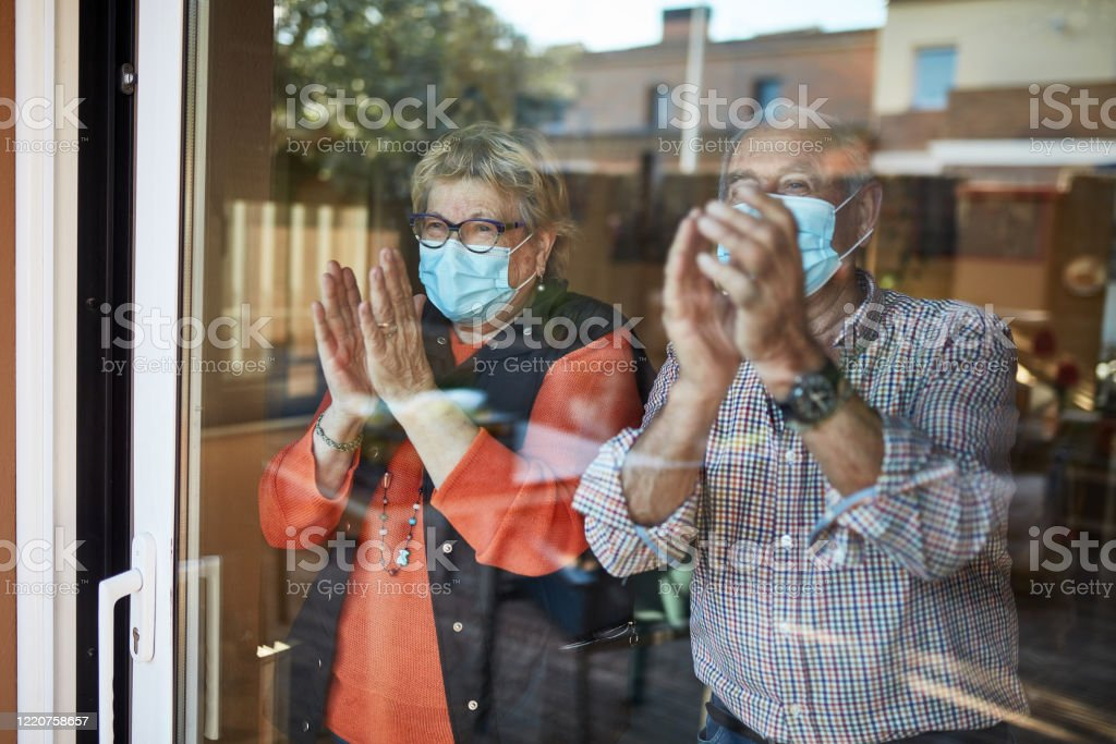 Senior couple on their 70s clapping hands at home in quarantine covid-19 Senior couple in self isolation looking through the window at home clapping. They are showing their support for all the workers and helpers who are helping during the COVID-19 outbreak. 70-79 Years Stock Photo