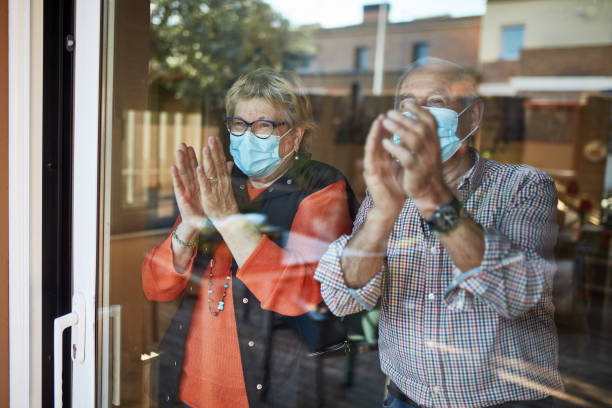 senior couple on their 70s clapping hands at home in quarantine covid-19 - old men window imagens e fotografias de stock