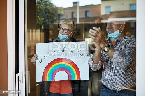 Senior couple on their 70s clapping hands at showing a hand drawn rainbow at home in quarantine. They are showing their support for all the workers and helpers who are helping during the COVID-19 outbreak.