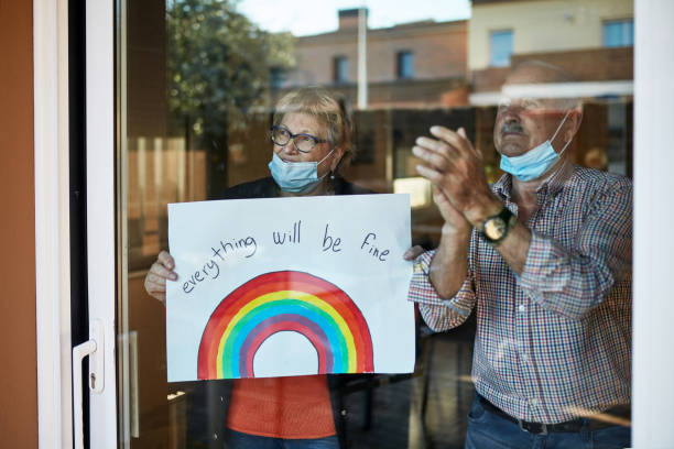 senior couple on their 70s clapping hands at showing a hand drawn rainbow at home in quarantine - old men window imagens e fotografias de stock
