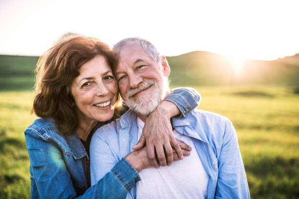Senior couple outside in spring nature at sunset. Happy senior couple outside in spring nature at sunset. senior couple stock pictures, royalty-free photos & images