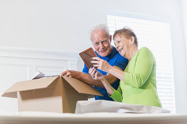 seniorenpaar packen box, schaut an bilderrahmen - stellenabbau stock-fotos und bilder