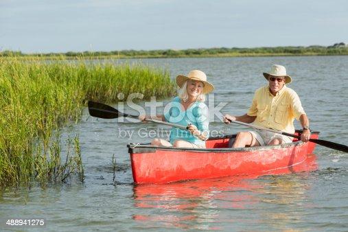 istock Senior couple paddling canoe on water 488941275