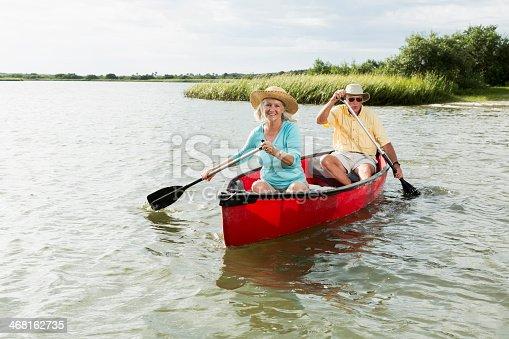 istock Senior couple paddling canoe with oars 468162735