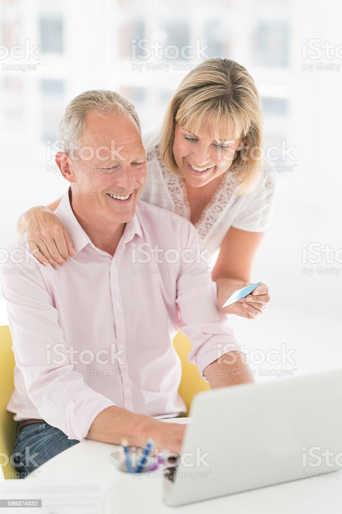 Senior couple paying bills online stock photo
