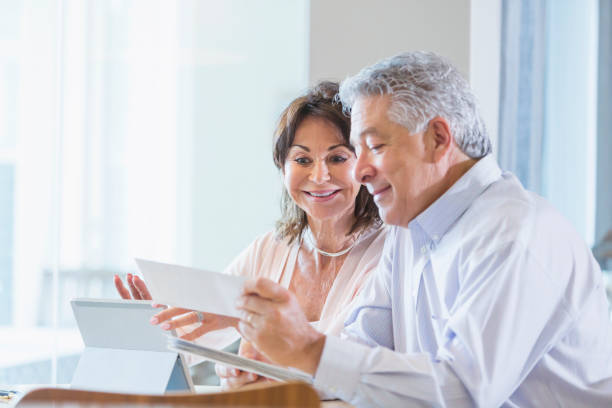 Senior couple paying bills online stock photo