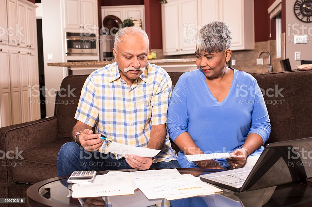 Indian man and African descent woman, senior adult couple work...